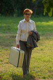 Die Frau, gealtert mit einem Koffer in ihrer Hand, geht entlang den ro Stockbilder