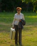 Die Frau, gealtert mit einem Koffer in ihrer Hand, geht entlang den ro Lizenzfreie Stockfotos