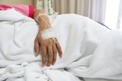 Die Frau geduldige ` s Hand, welche die Salzlösung empfängt lizenzfreies stockbild