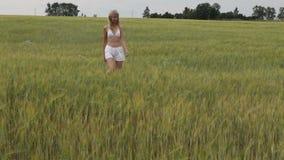 Die Frau geht über das Feld von grünen Ohren Stockfotografie