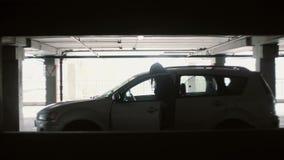 Die Frau geht über den Parkplatz und sitzt in ihrem Auto Frau öffnen die Tür des Autos, entfernen Signalisieren stock footage