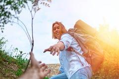 Die Frau gibt ihrem Freund ihre Hand, um die Leiste zu klettern Das Konzept der Freundschaft und der Rechtshilfe Ansicht von unte stockfotografie