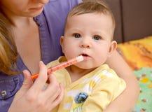 Die Frau gibt zur kranken Babymedizin mittels des batcher behandlung Lizenzfreies Stockbild