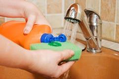 Die Frau gießt eine Abwaschflüssigkeit Stockbilder