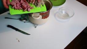 Die Frau gießt gekochtes Fleisch in die Fleischsuppe Suppe Saltwort Bestandteile für das Kochen sind auf dem Tisch stock video