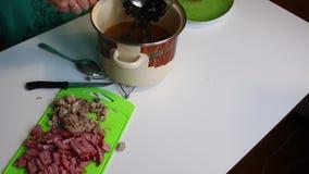 Die Frau gießt Oliven in die Fleischsuppe Suppe Saltwort Bestandteile für das Kochen sind auf dem Tisch stock video footage