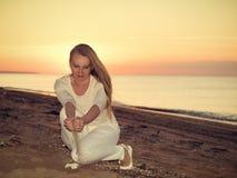 Die Frau gießt Sandhände bei Sonnenuntergang auf dem Meer Lizenzfreies Stockfoto
