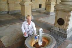 Die Frau gießt Wasser von einer Mineralquelle in Karlovy Vary lizenzfreie stockfotografie