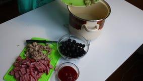Die Frau gießt in die zerriebenen in Büchsen konservierten Gurken des Fleisches Suppe Suppe Saltwort Bestandteile für das Kochen  stock video