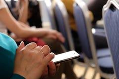 Die Frau hält das Telefon in ihrer Hand im Konferenzsaal und möchte die Mitteilung nennen oder aufpassen lizenzfreie stockfotos