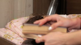 Die Frau hört auf zu lesen und küsst die Tochter auf einer Backe Die Märchen für die Nacht Ablesen für die Nacht stock footage
