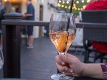 Die Frau halten halb voll spritz Getränk in einem Glas draußen an einem Restaurant lizenzfreies stockfoto