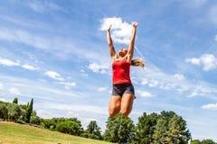 Die Frau hoch springend, um den Himmel im grünen Park zu erreichen Lizenzfreie Stockbilder