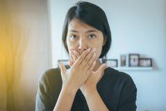 Die Frau, die ihren Mund bedeckt und riechen ihren Atem mit den Händen, schlechten Geruch stockbild