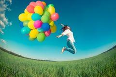 Die Frau im Frühjahr springend mit Feld der Spielzeugballone Stockfoto
