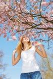 Die Frau im Frühjahr springend unter Kirschbaum Lizenzfreies Stockfoto
