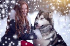 Die Frau im grauen Mantel mit einem Hund oder einem Wolf Abstrakte Fantasiehintergründe mit magischem Buch schneefälle Weihnachte Lizenzfreies Stockbild
