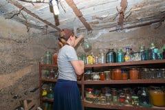 Die Frau im Keller ist, das Mädchen zubereitet Nahrung für den Winter, Konserven in den Glasgefäßen auf dem Gestell grauhaarig lizenzfreies stockfoto