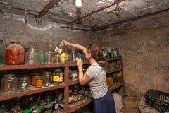 Die Frau im Keller ist, das Mädchen zubereitet Nahrung für den Winter, Konserven in den Glasgefäßen auf dem Gestell grauhaarig stockfoto