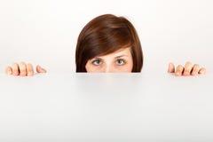 Die Frau ist das Verstecken besorgt hinter der Tabelle stockfotos