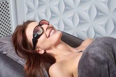 Die Frau kam zum Verfahren des Laser-Haarabbaus Sie ` s, das Schutzbrillen trägt Sie liegt auf der Couch in a lizenzfreies stockfoto