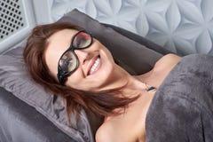 Die Frau kam zum Verfahren des Laser-Haarabbaus Sie ` s, das Schutzbrillen trägt Sie liegt auf der Couch in a lizenzfreie stockfotografie