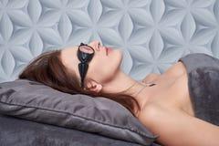 Die Frau kam zum Verfahren des Laser-Haarabbaus Sie ` s, das Schutzbrillen trägt Sie liegt auf der Couch in a lizenzfreie stockbilder