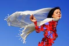 Die Frau kleidete in den Herbstblättern die Jahreszeit genießend an Lizenzfreie Stockfotos
