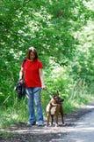 Die Frau kleidete in den Jeans und in einem roten T-Shirt gehend mit einem Hund an lizenzfreies stockbild