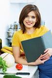 Die Frau kochend, die in der Küche steht, decken Sie Rezept vom Menü mit Schilf Lizenzfreie Stockbilder