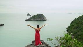 Die Frau kostet an der Spitze der Insel, die Hände gerade gerichtet wird Alleine mit der Natur Die Frau in einem roten Kleid am F stock footage
