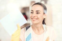 Die Frau lächelt und wischt das Fenster zu Hause ab lizenzfreie stockbilder