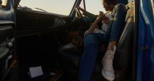 Die Frau, die an liegt, bemannt Schoss in einem Kleintransporter am Strand 4k stock video footage