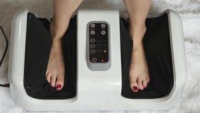 Die Frau macht eine Fußmassage unter Verwendung eines elektronischen Fuß Massager Der Schönheitsbegriff und die Gesundheit stock video