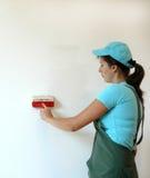 Die Frau malt die Wand Stockfotografie