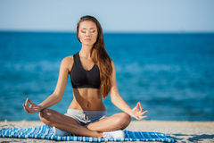 Die Frau meditiert auf einem Strand nahe dem Meer lizenzfreie stockfotos