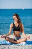 Die Frau meditiert auf einem Strand nahe dem Meer lizenzfreies stockfoto