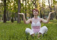 Die Frau meditiert im Park Lizenzfreie Stockfotos
