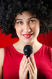 Die Frau mit Afrofrisur singend im Karaoke Lizenzfreie Stockfotos