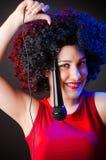 Die Frau mit Afrofrisur singend im Karaoke Lizenzfreies Stockfoto