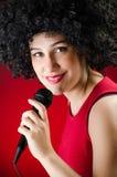 Die Frau mit Afrofrisur singend im Karaoke stockfoto