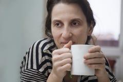 Die Frau mit einem Becher trinkt Tee Lizenzfreie Stockfotos