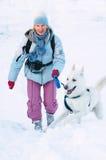 Die Frau mit einem Hund im Winter Lizenzfreies Stockfoto