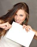 Die Frau mit einem leeren Blatt des Papiers in den Händen Lizenzfreie Stockfotografie
