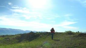 Die Frau mit einem roten Rucksack geht Grün ein Leid hinauf Ansicht von Schneebergen stock video footage