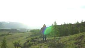 Die Frau mit einem roten Rucksack geht Grün ein Leid hinauf Ansicht von Schneebergen Morgen Sun Die Frau in den Händen hat Stöcke stock footage