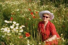 Die Frau mit Mohnblumen und Kamille Lizenzfreies Stockfoto