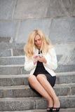Die Frau mit Telefon sitzen auf einer Leiter Lizenzfreies Stockfoto