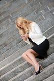 Die Frau mit Telefon sitzen auf einer Leiter Lizenzfreie Stockfotografie