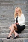 Die Frau mit Telefon sitzen auf einer Leiter Lizenzfreie Stockfotos